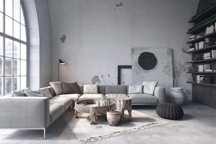 déco de style loft dans un salon aux murs gris clair et plancher imitation béton aménagé avec canapé d'angle couvert de coussins de couleurs neutres