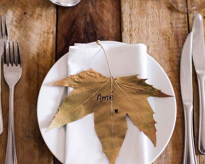 feuille morte marron clair avec prénom invité écrit au feutre, table bois brut, assiettes et serviette blanches