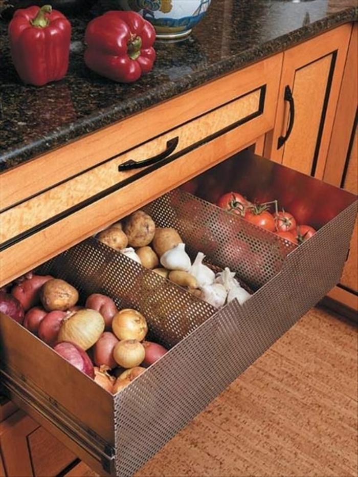rangement tiroir, amenagement de placard, oignons et tomates rangés dans un placard profond, meuble avec plan de surface aux effets marbrés noirs et blancs