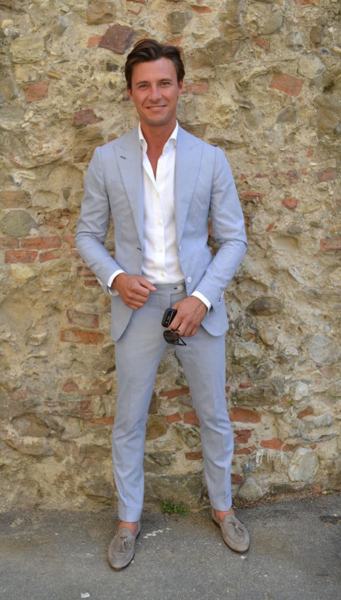 costume gris clair d'une élégance nonchalante, porté avec une chemise blanche à col déboutonné et des mocassins en velours gris