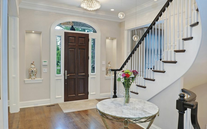 maison de luxe moderne, déco entrée maison, table ronde marbrée, porte d'entrée en bois foncé, escalier