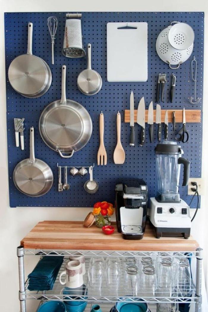 amenagement placard cuisine, rangement coulissant cuisine, mur couvert de revetement en métal bleu aux effets ajourés, ustensiles suspendus au-dessus d'une table avec la machine a café et le shaker