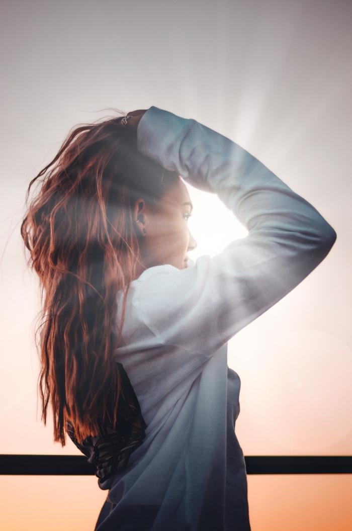 effet rayons du soleil sur couleur de cheveux, jeune femme aux cheveux longs de couleur foncée et aux reflets cuivrés