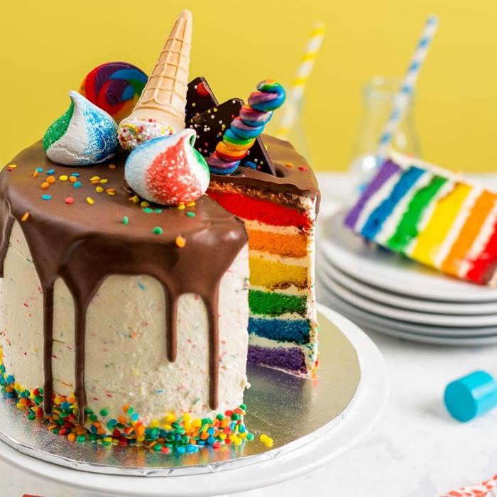 idée de décoration originale de gateau arc en ciel au glaçage coulant au chocolat, avec des meringues multicolore et des cornets de glace dessus