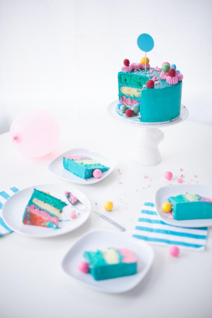 recette de layer cake à plusieurs couches colorées , recouvert de glaçage turquoise et décoré aves des fleurs en glaçage