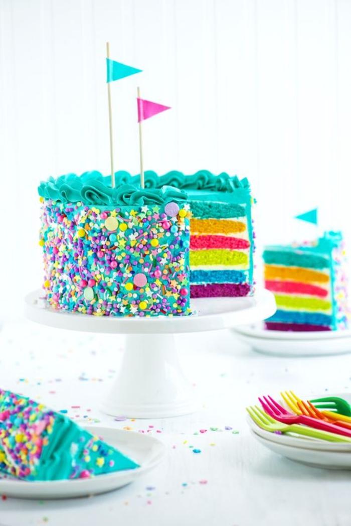 idée pour un joli gateau multicolore au glaçage bleu turquoise, décoré avec des confettis en sucre et des piques drapeaux