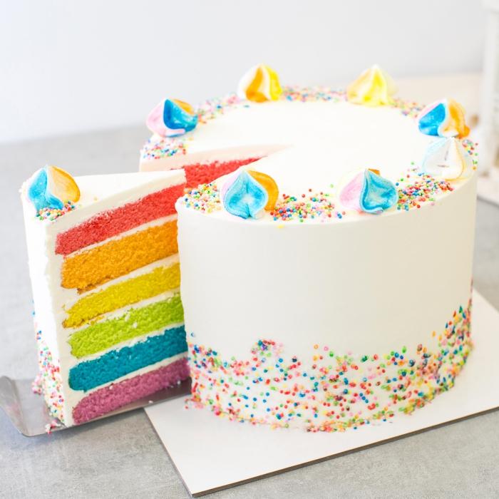recette de layer cake à base de plusieurs génoises colorées, au glaçage simple à l'extérieur, décoré avec des meringues