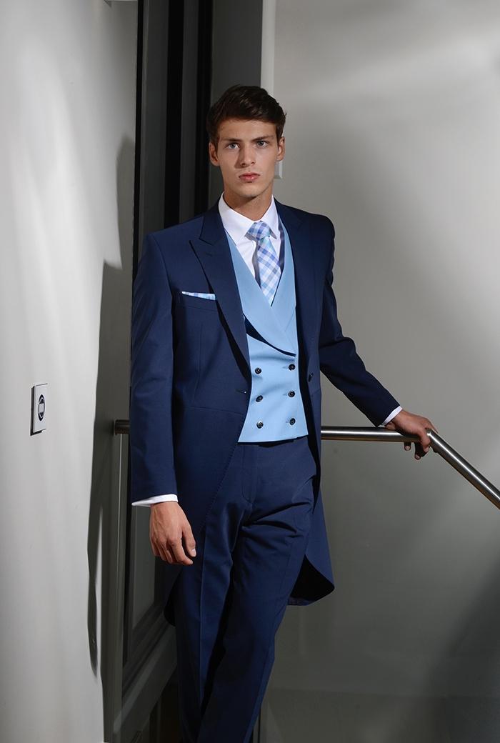 modèle de redingote homme bleu marine classique avec un gilet bleu pastel associé à une cravate à carreaux aux même nuances