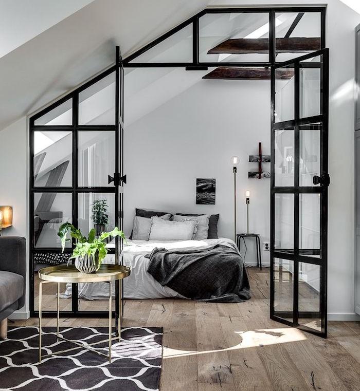 verrière industrielle noire qui s ouvre sur uen chambre à coucher gris et blanc dotée de plancher bois brut, murs blancs, salon à meubles gris