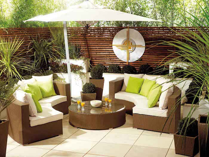 terrasse recouverte de carrelage canapés et table basse rotin, coussins d assise blancs et coussins décoratifs vert pistache, plantes en pots et bacs à fleurs, séparation en bois