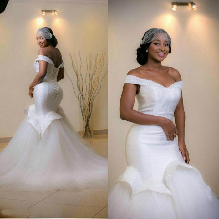 mariée avec voilette, femme afro-américaine, robe de mariée sirène, petites perles blanches autour du décolleté, tulle traînant par terre