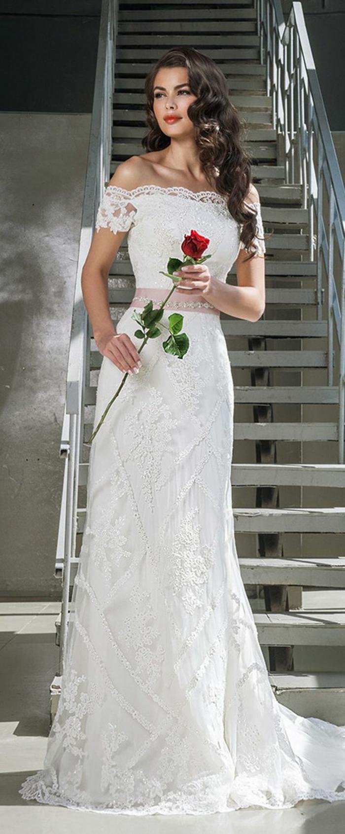 robe de mariée près du corps, épaules tombantes en dentelle, ceinture rose en satin, décolleté bateau, manches courtes 3-4, silhouette sublimée