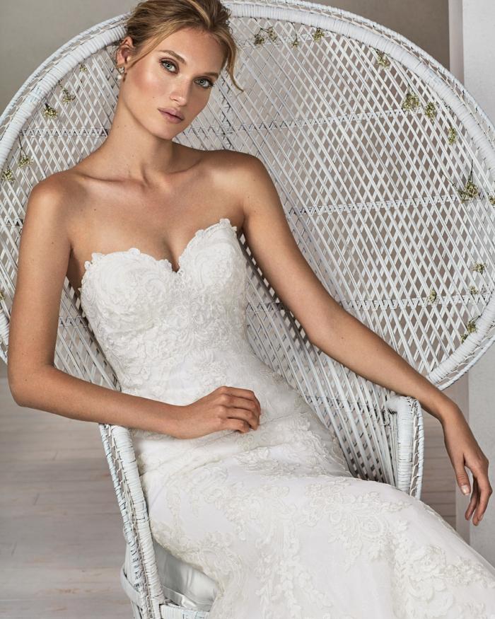 robe sirene mariee avec bustier, dentelle blanche, mariée assise dans un fauteuil en rotin blanc avec dossier très large type éventail, robe de mariée sirène