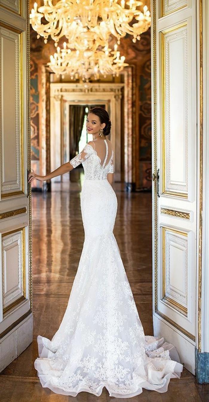 coupe avec des manches en dentelle blanche 3-4 ,robe de mariée sirene, traîne très longue, robe sirene mariee, ambiance de château, salle de bal avec des gros luminaires style Renaissance