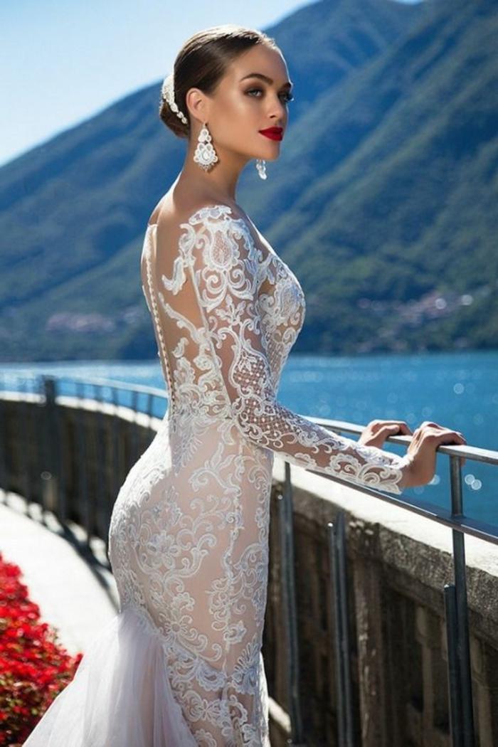 modèle aux arabesques fins comme des tatous sur la peau, robe de mariée sirene, robe de mariée près du corps, manches longues, tulle qui part des fesses derrière