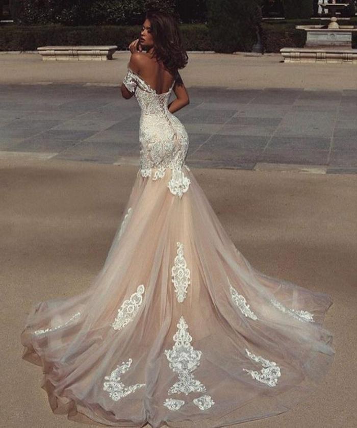 en couleur écru, robe de mariée bustier, robe mariage sirene, traîne en tulle blanc avec des arabesques en dentelle blanche en relief, manches 3-4 courtes tombantes