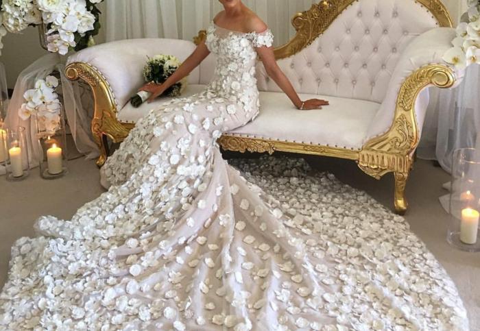 robe sirene mariee, traîne très longue, robe de mariée fourreau, ambiance très luxueuse avec canapé au tissu matelassé en couleur rose délicat