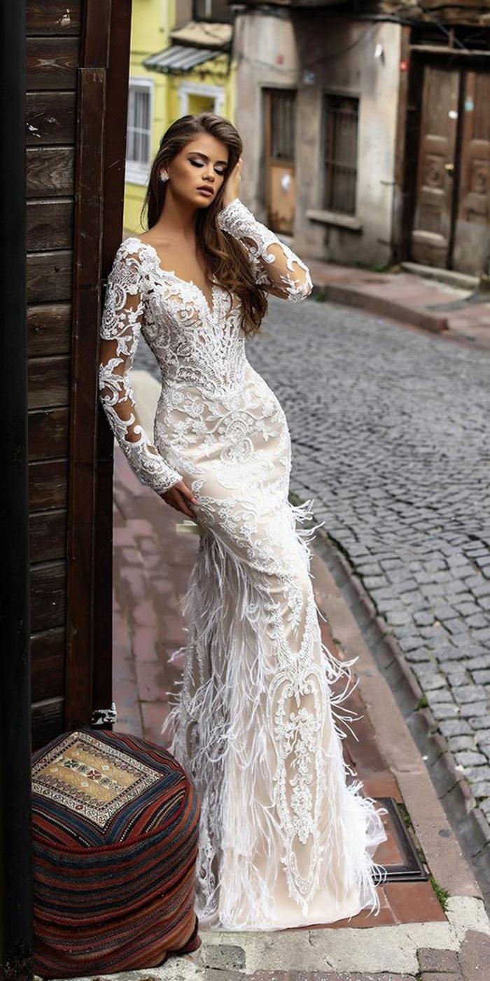 robe de mariée sirene, modèle aux manches longues en dentelle blanche, plumes blanches autruche sur la partie de la jupe, silhouette glamour et sexy