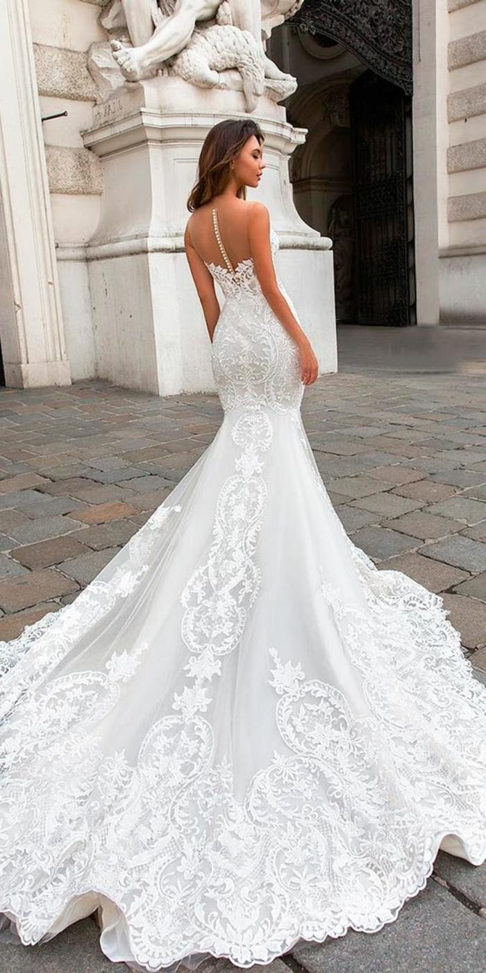 un modèle de robe de mariée sirène, boutons blancs dans le dos, bras et épaules nus, robe de mariée moulante, grande classe