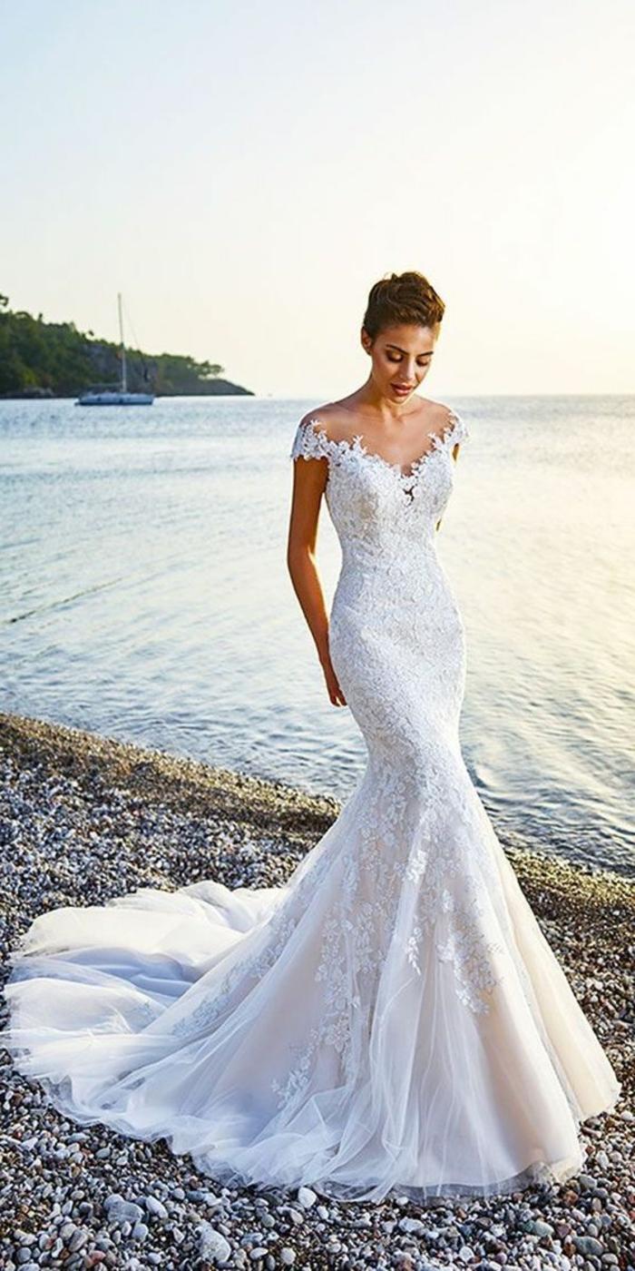 femme avec la silhouette svelte et mince, robe de mariée sirene dentelle, épaules dénudées semi-tombantes, partie basse en éventail