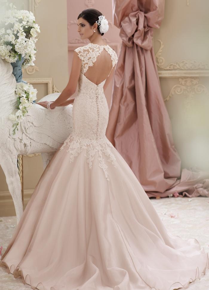modèle en rose saumon, robe de mariée sirène, dos nu en forme de cœur, dentelle somptueuse, tissu satiné, traîne longue, fleur en dentelle dans les cheveux
