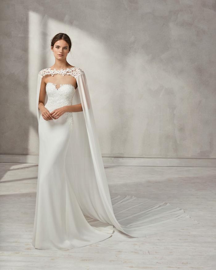 robe de mariée moulante, silhouette minimaliste, sans ornements, cape longue en satin blanc avec les épaules décorées de grosse dentelle blanche aux motifs fleuris
