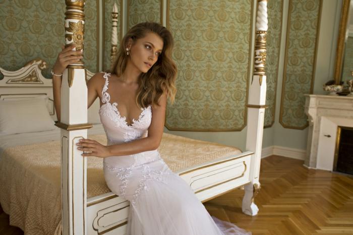 robe de mariée sirene, bretelles en dentelle blanche, décolleté grand ouvert en V, robe de mariée moulante, mariée rêveuse assise sur un grand lit massif