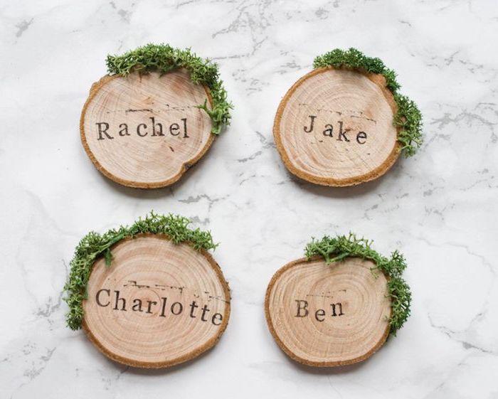 rondin de bois décoré de mousse aux bords avec le prénom de l'invité marquée à l encre dessu