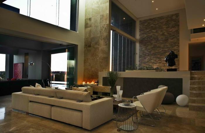 grand séjour contemporain, canapé beige, chaises design, décoration intérieure salon extravagante, dallage mural et dallage au sol