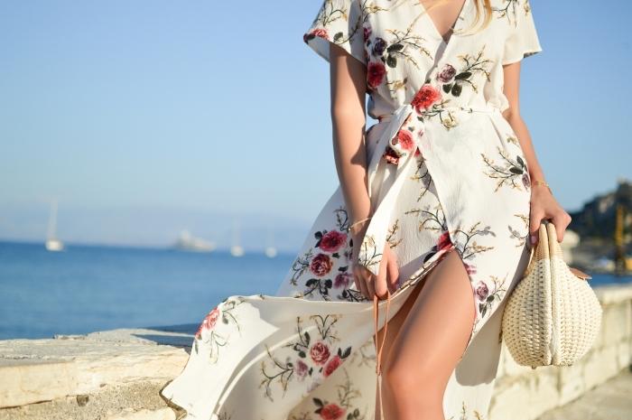 modèle de robe longue blanche aux manches courtes avec décoration florale, sac a main blanc et beige pour plage