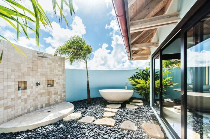 zone douche au dernier étage d'un immeuble, palmier et arbre, petit buisson, sol recouvert de cailloux noirs, ambiance spa, plante pour salle de bain, plante qui absorbe l'humidité