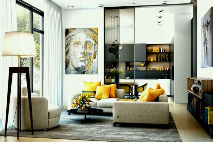 salon contemporain et gris et blanc, coussins jaunes, portrait art, grande lampe quatre pieds, verrière atelier donnant sur cuisine