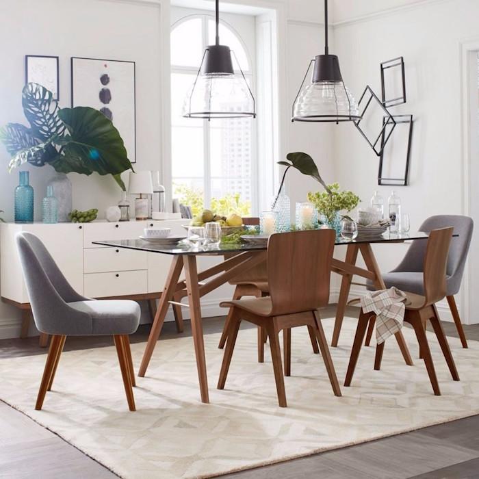 chaises et table à manger scandinave en verre et bois design et éclairage suspendu et murs blancs