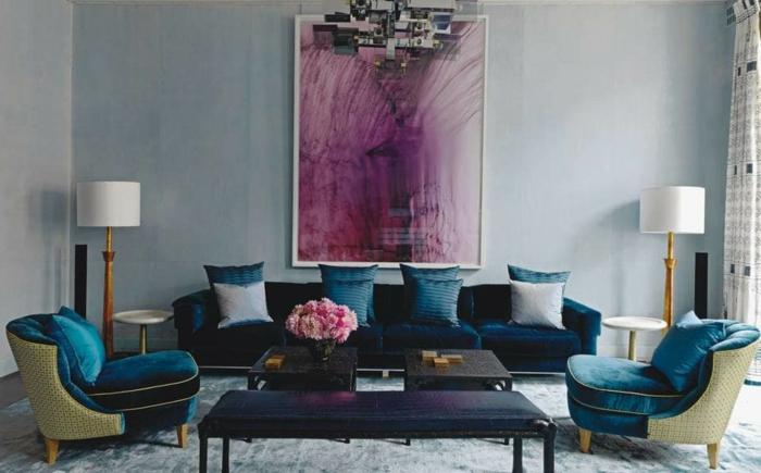 tapis gris moelleux, canapé bleu foncé avec plusieurs coussins, deux lampes à abat-jour
