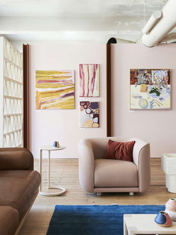 décoration intérieure salon féminine, peintures artistiques, fauteuil gris, petite table blanche, fauteuil marron, sol en bois blanc