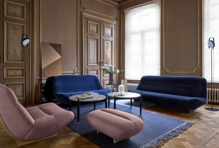 salon en bleu et rose, fauteuil et tabouret roses, canapés bleus, tapis bleu, murs peints rose cendré