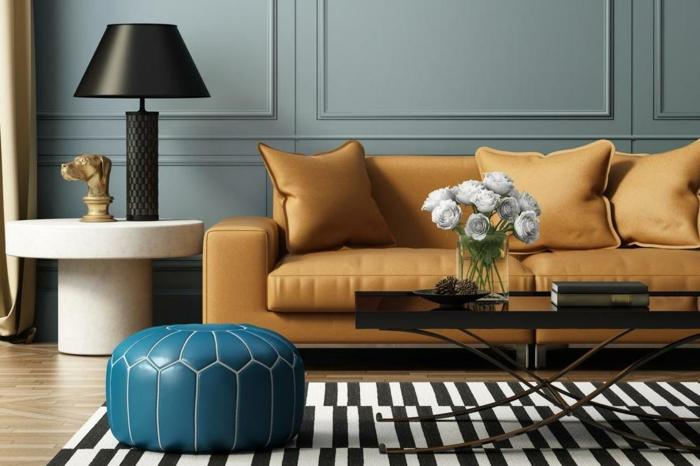 décoration intérieure salon, tapis rayé en noir et blanc, sofa moutarde, lampe blanche avec une grande table à abat-jour, panneaux muraux bleu canard