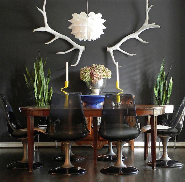 déco de salle à manger avec bois de cerf blancs, table en bois ovale rétro et chaises vintage plastique noire