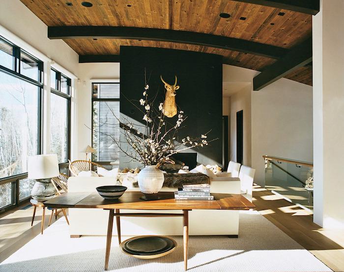 ensemble salon salle à manger avec déco design et poutres apparentes noir avec plafond en bois en tete de cerf en or