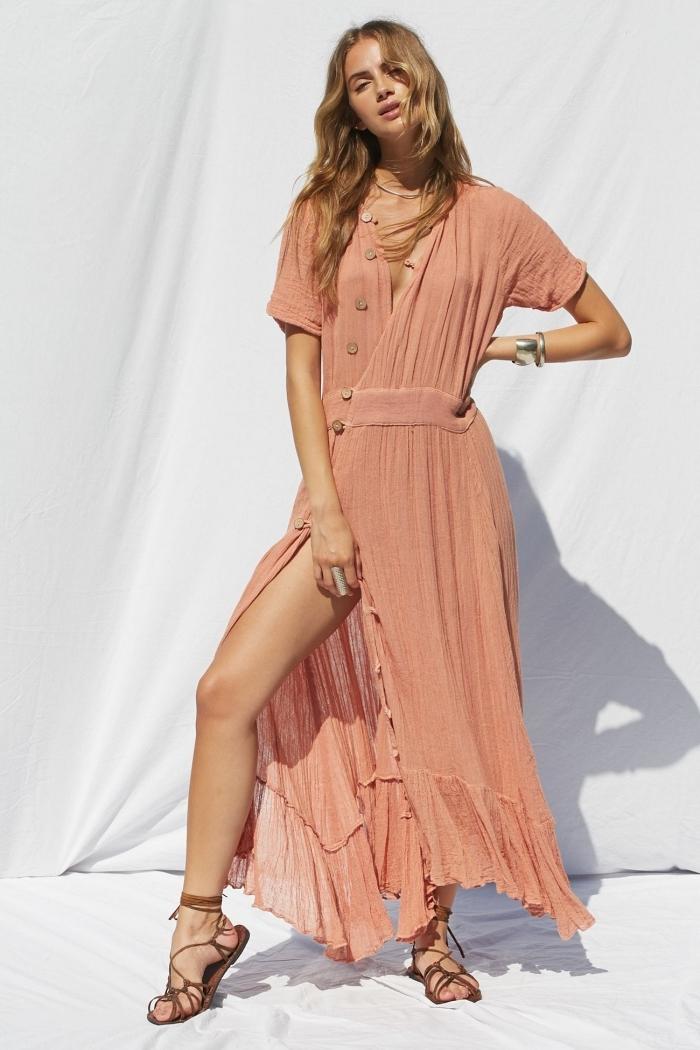 mode femme plage avec une robe corail pastel longue à design asymétrique avec décolleté en V boutonné et manches courtes