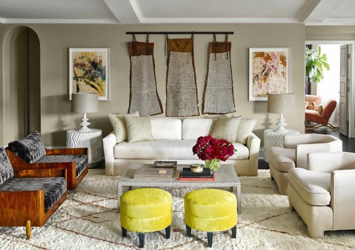 tapis berbère, deux tabourets jaunes, chaises en bois et textile, sofa blanc et deux fauteuils blancs et teintures murales