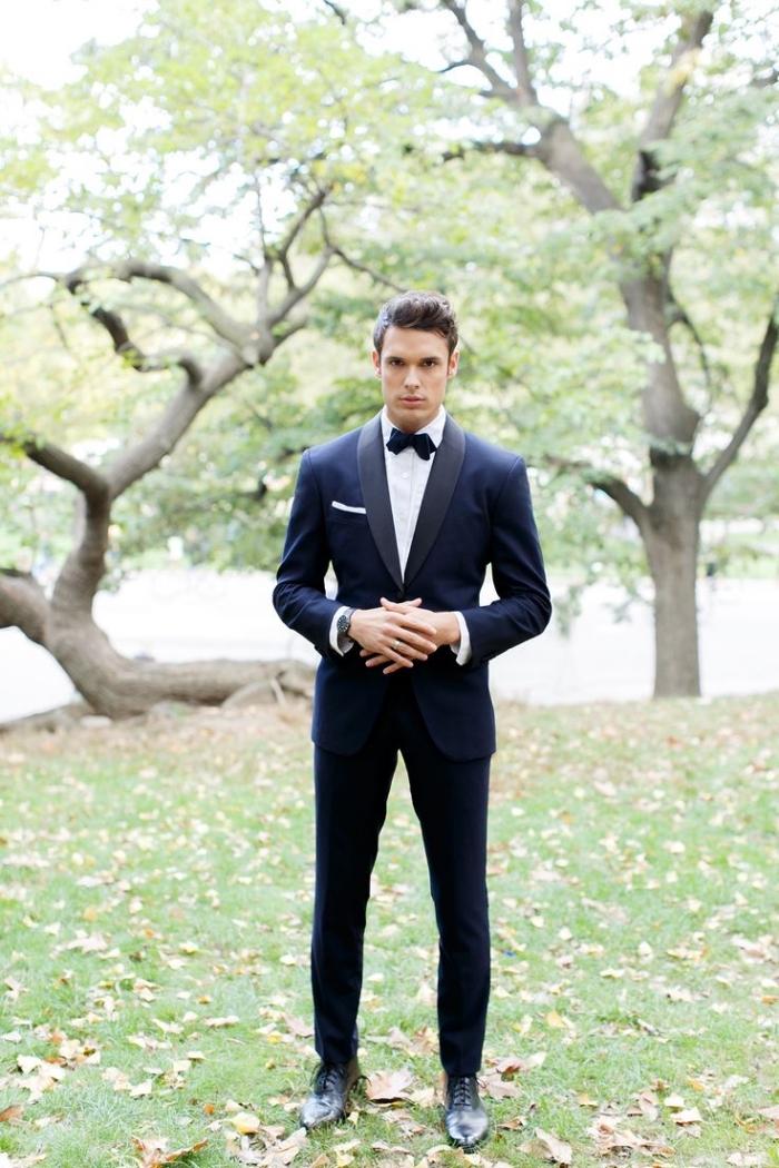 un look sobre et élégant en costard mariage noir de type smoking bien coupé assorti avec un noeud papillon noir très pointu