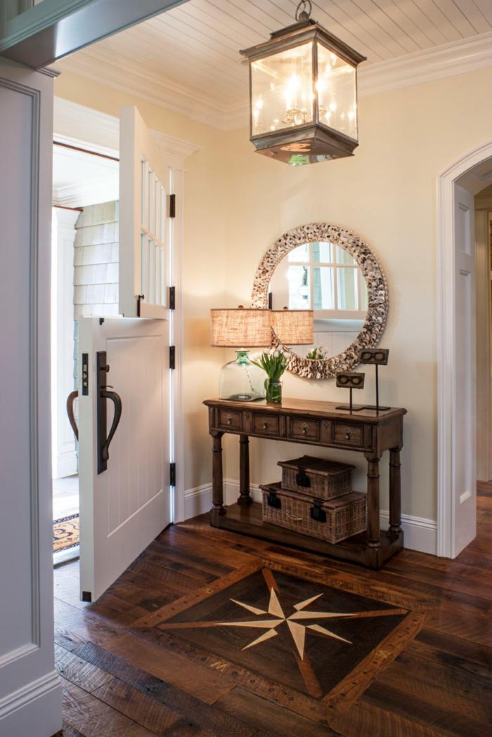 créer une entrée dans un espace ouvert, console vintage, paniers rustiques, miroir rond, luminaire lanterne miraculeux, sol en planches de bois et porte d'entrée blanche