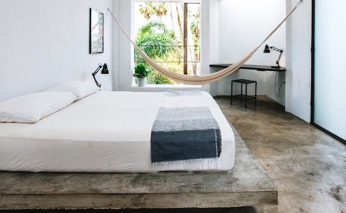 sol effet beton et matelas blanc sur une plate forme béton, murs blancs, bureau style industriel noir et tabouret