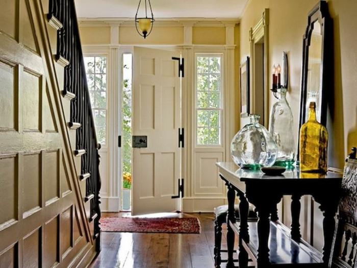 peinture de couloir en couleur pâle, porte blanche, grand miroir noir, bocaux en verre