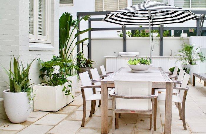 salle à manger extérieure en table et chaises bois, carrelage beige, plantes en pots et bacs, pergola moderne grise, parasol noir et blanc