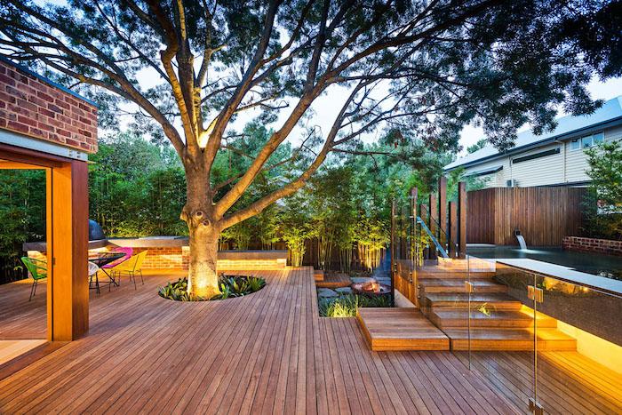 idée terrasse bois composite avec un grand arbre au milieu, cloture bois bordé de bambous, éclairage extérieur moderne