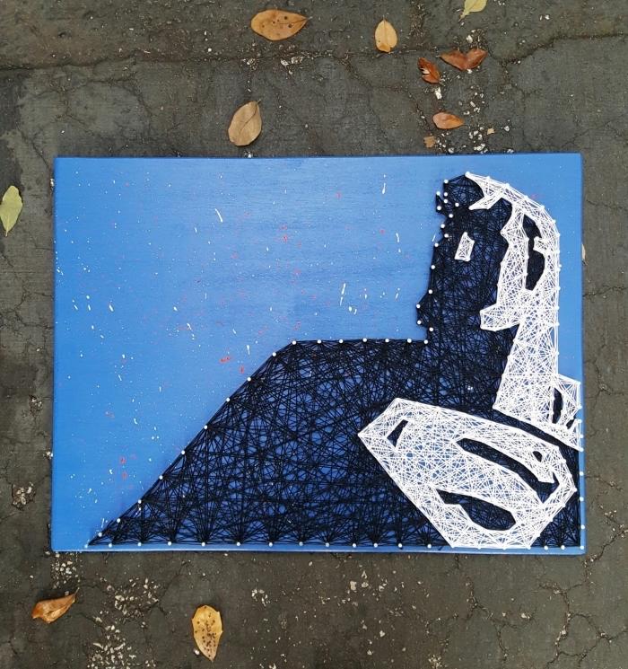 utiliser un gabarit fil tendu pour créer un tableau décoratif peint en bleu avec silhouette d'inspiration superman