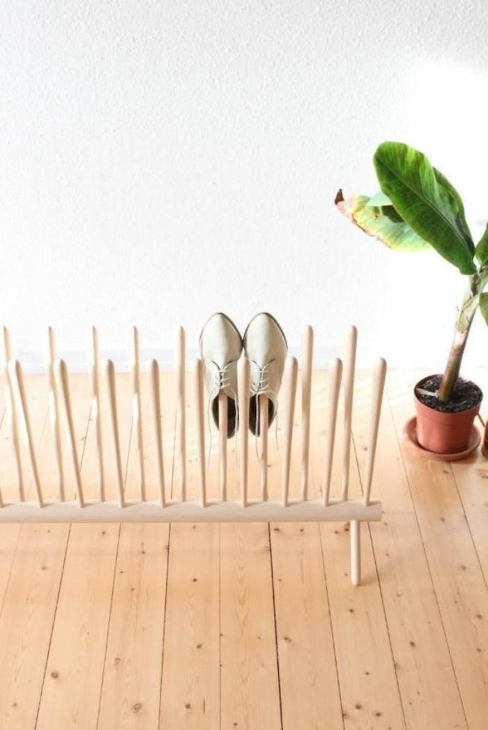 un petit meuble chaussure réalisé entièrement en bois, au design malin unique avec ses tiges en bois nature