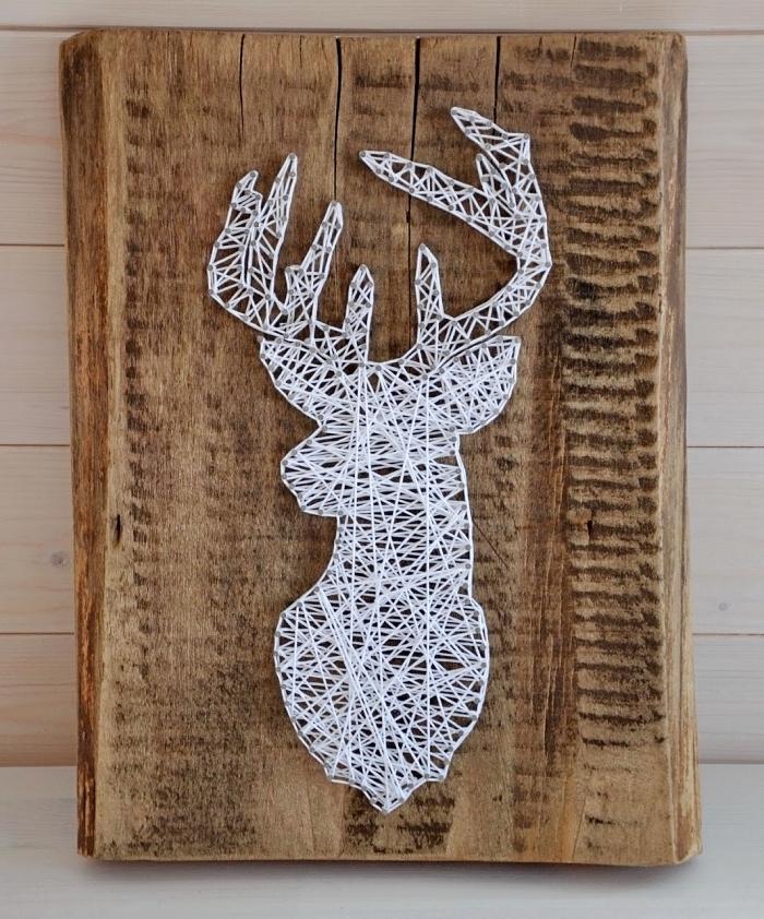 idée bricolage facile avec un panneau de bois massif décoré de fil blanc et de clous qui forme une tête de cerf